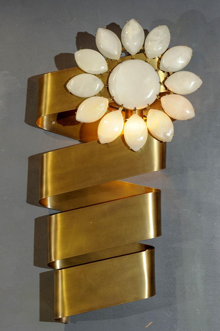 This original wall lights is made of brass, with an alabaster flower. Each sconces wears a light bulb. A pair is available.