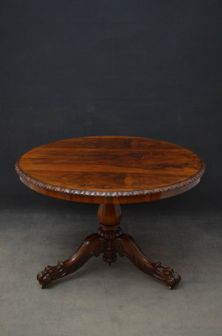 Sn5114 Fine quality 19th century centre or dining table in rosewood, having tilt top with fabulous grain and crisply carved edge, standing on vase shaped column with three finely carved, downswept legs terminating in paw feet in original castors.