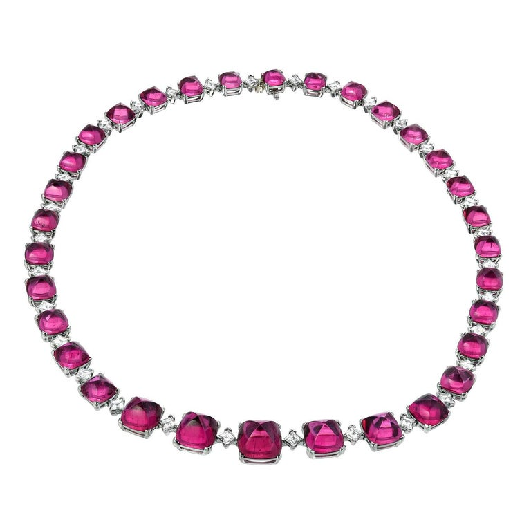 Superior 32 gradually custom-cut sugar loaf, cushion cut, cabochon Rubellite Tourmalines, weighing a total of 84.54 carats, are hand set in this one of a kind 8.42 carat total diamond necklace. Total length is 17 inches. Returns are accepted and