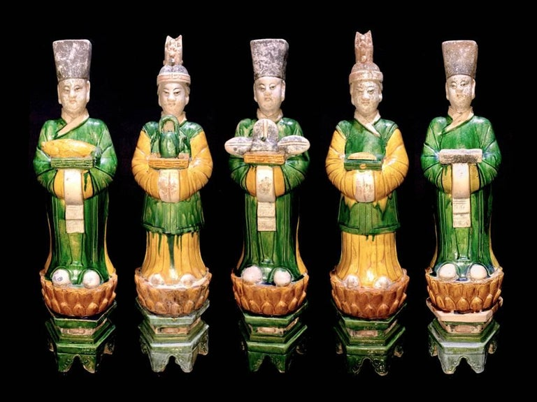 A stunning set of 5 graceful terracotta figurines from the Ming Dynasty '1368-1644' AD.  These elegant attendants are standing on a yellow glazed lotus flower over a high hexagonal green plinth and wear fine robes in matching green and yellow