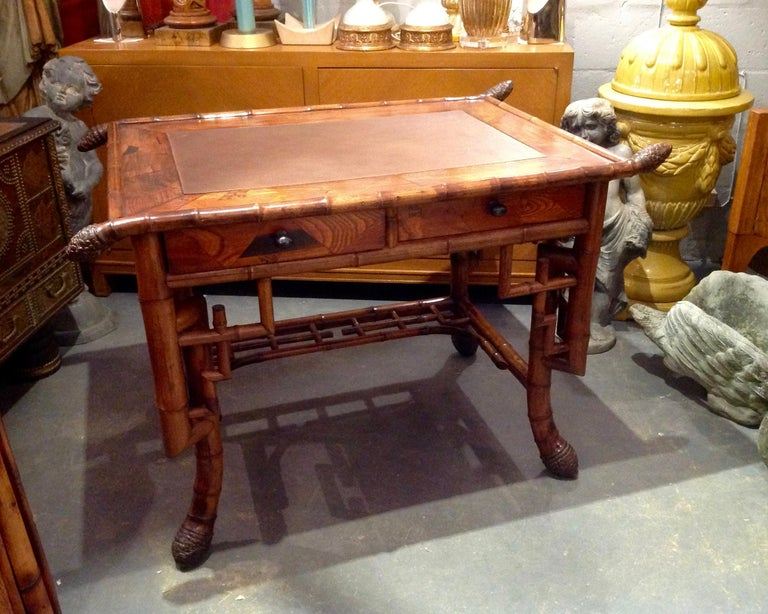 Superb quality and stylized bamboo appointed with inlays and a leather top. The desk is fashioned with 2 drawers and terminates with massive root feet. This aesthetic era piece may possibly be one of a kind.