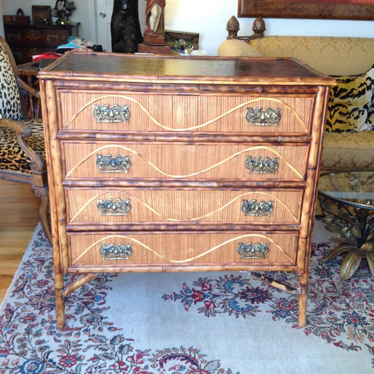 Details abound in this unusual English dresser with a tortoise like finish. The piece is appointed with an interesting lacquered top, bent bamboo drawer embellishments, and elaborate vintage hardware. The drawer interiors are finished and