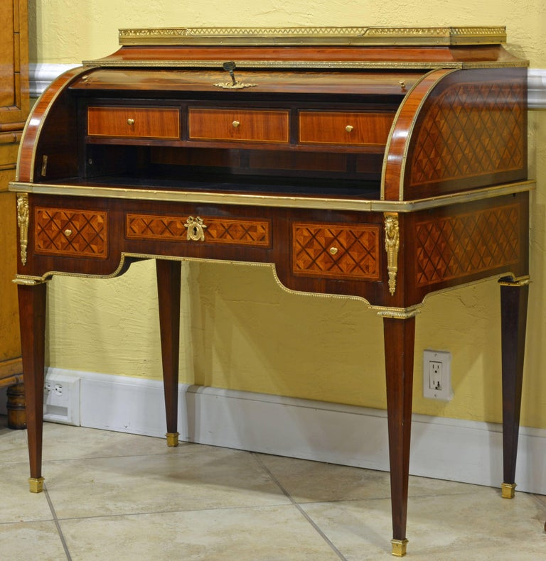 This fine cylinder desk in the style of Louis XVI features a three-quarter pierced brass gallery top mounted with red turquin marble a above a shaped pediment and the marquetry roll top enclosing an interior fitted with three drawers, three