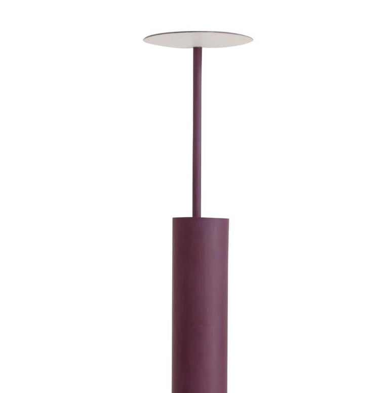 Defined by functional aesthetic, this lamp features a central cylindrical column containing a bright light source whose rays are reflected off the flat oval top supported by the adjacent, slender rod. Handcrafted of iron, this functional work of art
