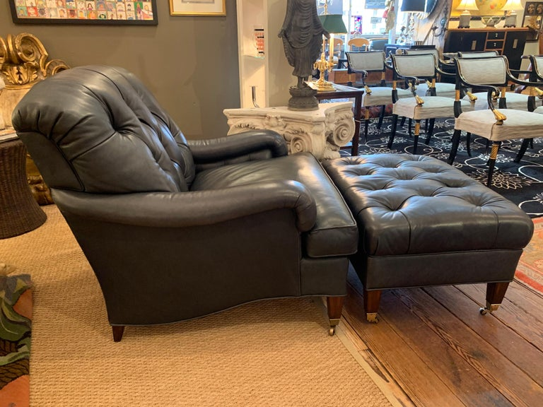 Super fetching and top of the line soft grey blue leather club chair and ottoman. The chair has a button tufted inside back and a wonderful added touch of tufting on the interior under the arms. Measures: Seat height 19.5 seat depth 22.