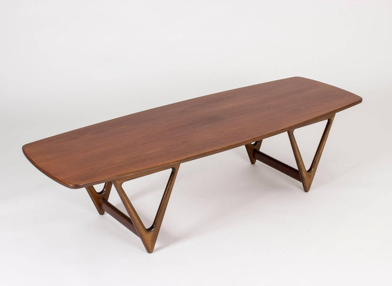 """Amazing """"Surfboard"""" coffee table by Kurt Østervig, with a long tabletop with sweeping teak veneer and cool, beautifully sculpted V-shaped legs. A real conversations piece."""