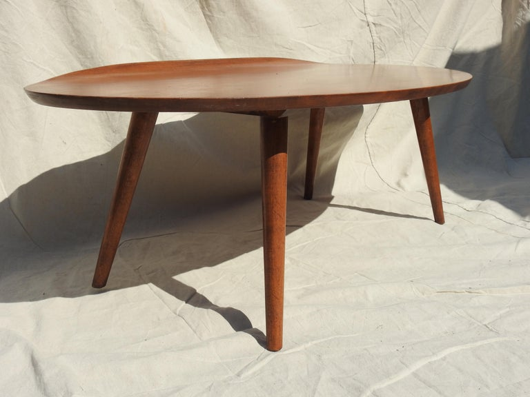 Gorgeous midcentury 1950s Russell Wright designed surfboard coffee or cocktail table with curved lip on one side. Beautiful warm toned walnut surfboard shape sitting on 4 tapered turned legs. Russell Wright Conant ball markings are on underside of