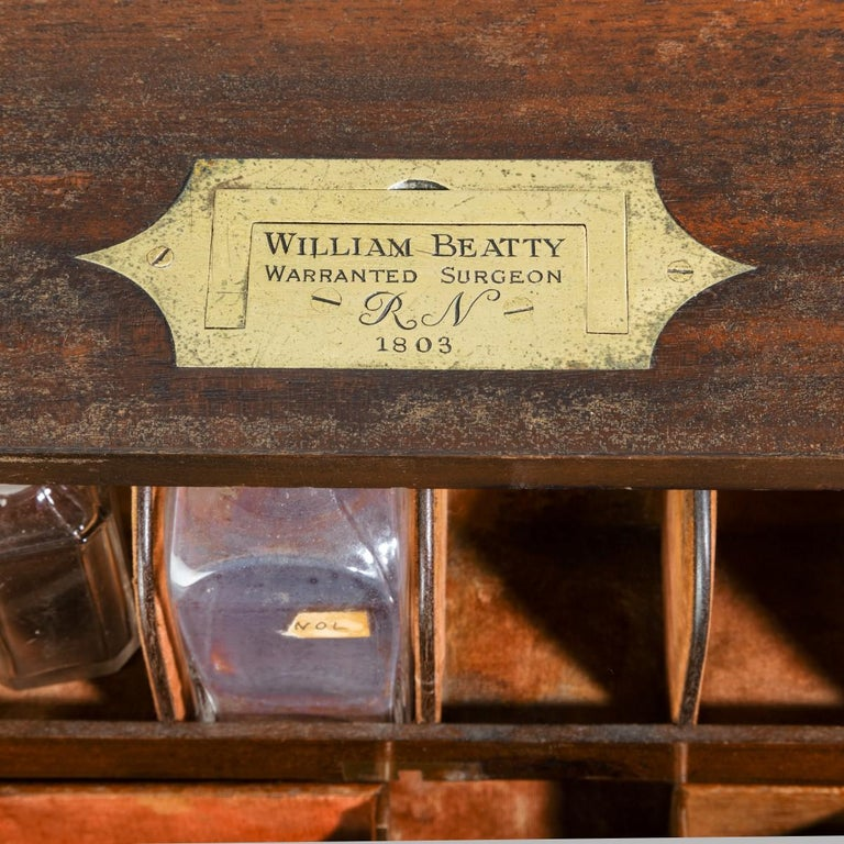 This naval surgeon's medicine cabinet is of rectangular form with two doors, each fitted with two rows of bottle racks, which open to reveal two long drawers and four racks, the reverse with a disguised sliding panel which has to be opened by a