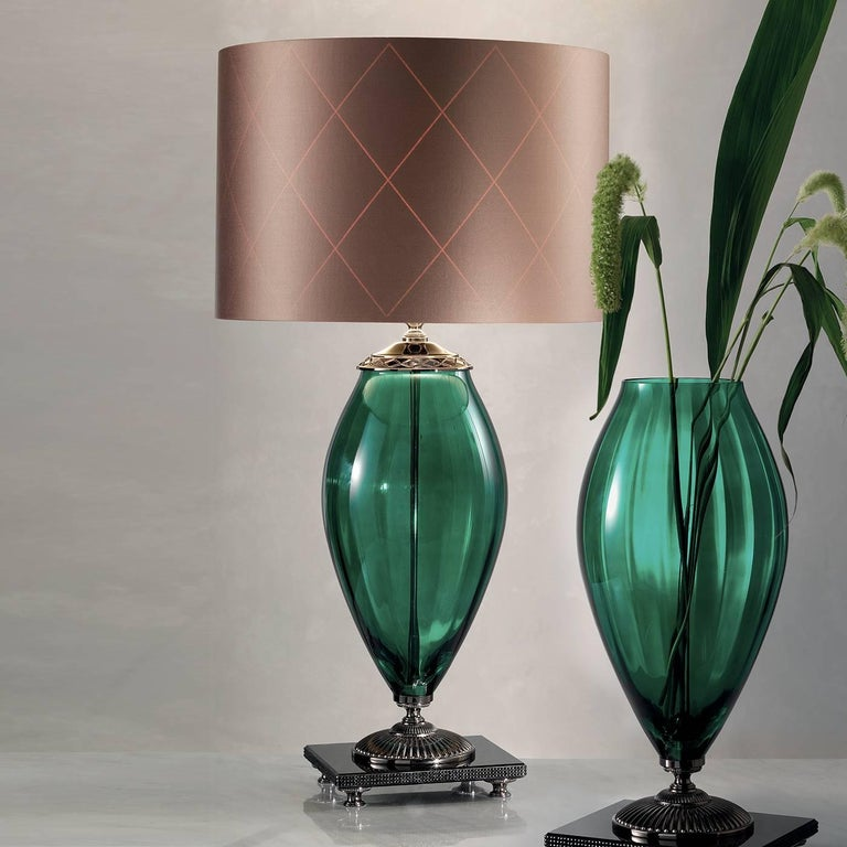 A glamorous accent perfect for any space, this eye-catching lamp showcases a green glass body with a gold-plated decorative accent around the top. Resting atop a black square marble base accented with black rhinestones, the lamp sits on an ornate