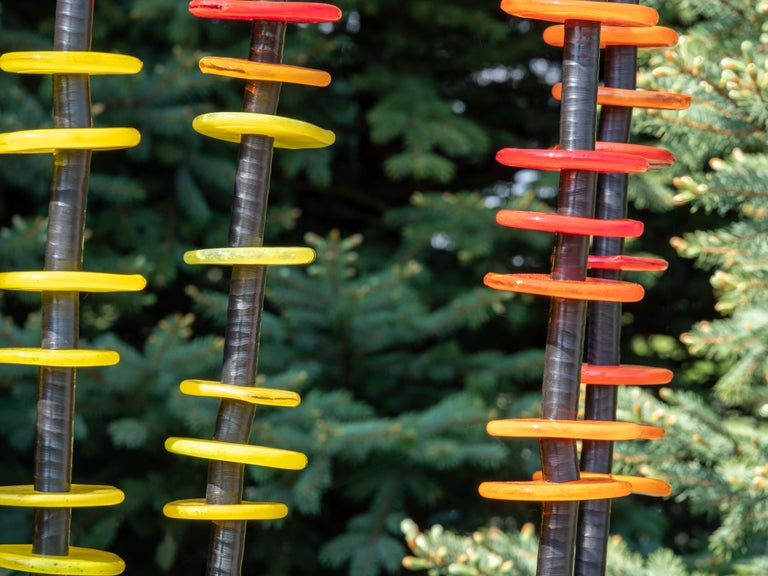 Hand blown glass rings of bright red, orange and yellow are stacked organically on seven stems in this brilliant outdoor sculpture by Susan Rankin. The stems are fixed to a steel plate and sway gently in the breeze.  Each column includes the hand