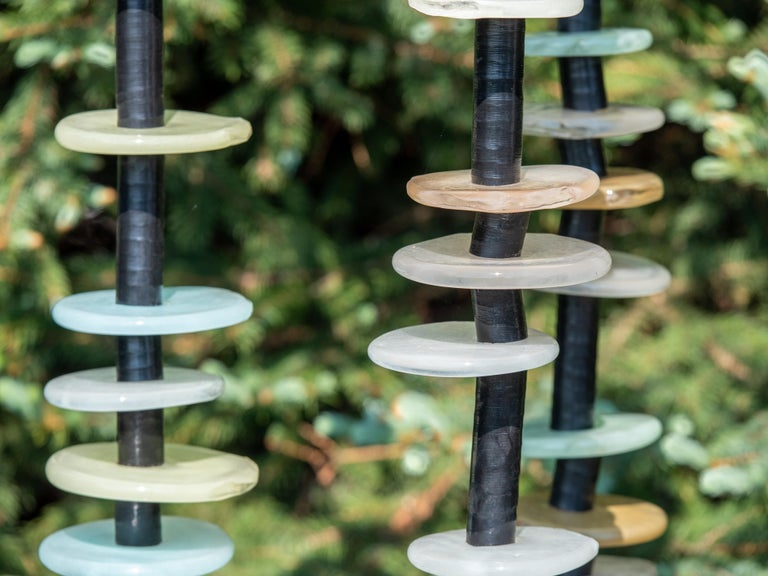 Hand blown glass rings of glowing soft blue, green, ivory, taupe and gray are stacked organically on three stems in this delightful outdoor sculpture by Susan Rankin. The stems are fixed to a steel plate and sway gently in the breeze.  Each column
