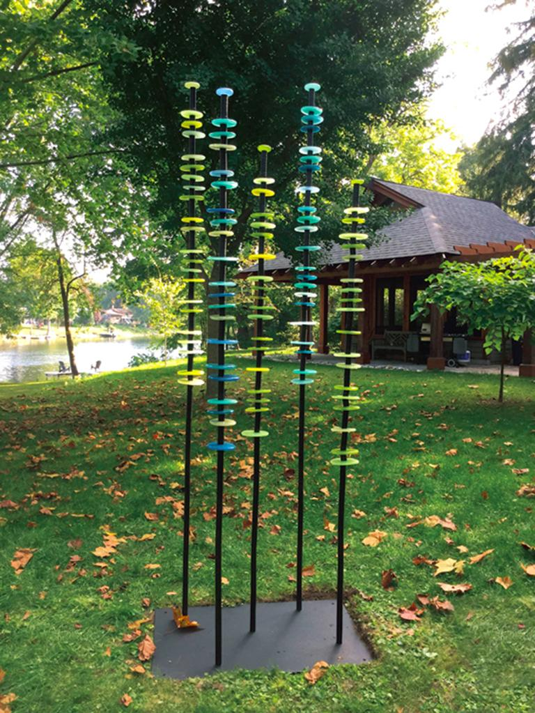 Hand blown glass rings of glowing blues and greens are stacked organically on seven stems in this charming outdoor sculpture by Susan Rankin. The stems that wave gently in the breeze are fixed to a steel plate. This work is available by commission.