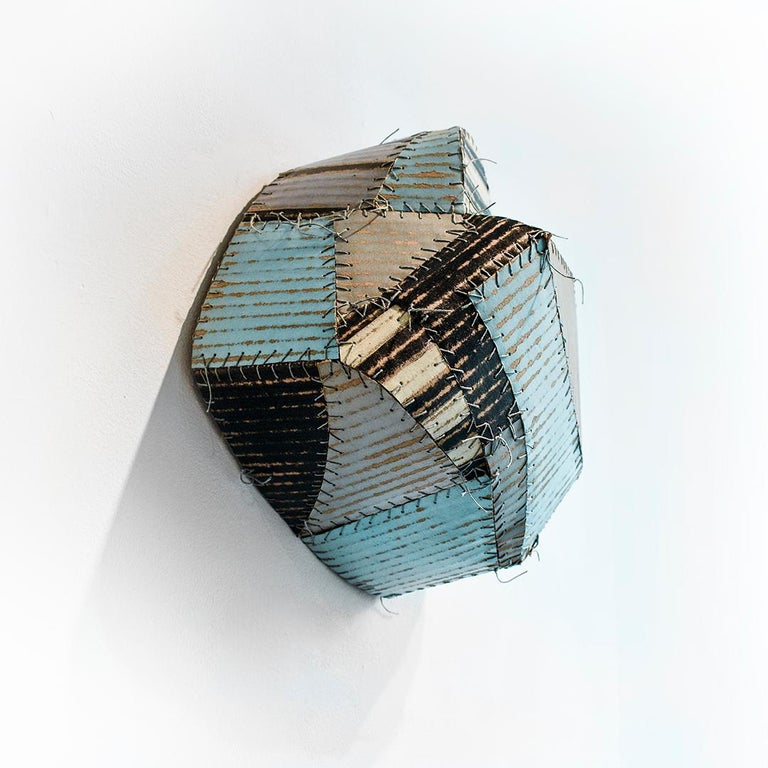 Abstract, folk art style, three dimensional wall sculpture in striped patterns of sky blue, black, white and grey