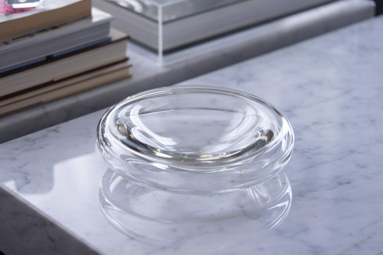 A beautifully crafted clear blown glass bowl or dish designed by father and son Alfredo & Flavio Barbini for Barbini Murano in 1972. Thick glass walls round out and downwards at its sides giving the piece the appearance of hovering above the