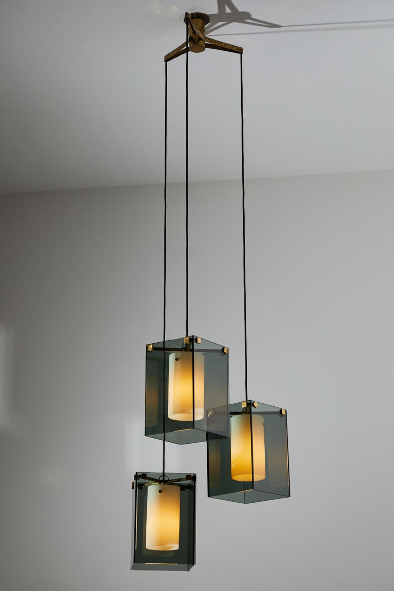 Suspension light by Max Ingrand for Fontana Arte. Designed and manufactured in Italy, circa 1960. Glass diffusers, brushed satin glass internal cylinders, brass armature and hardware. Custom brass ceiling plate. Rewire for U.S. junction boxes. Takes