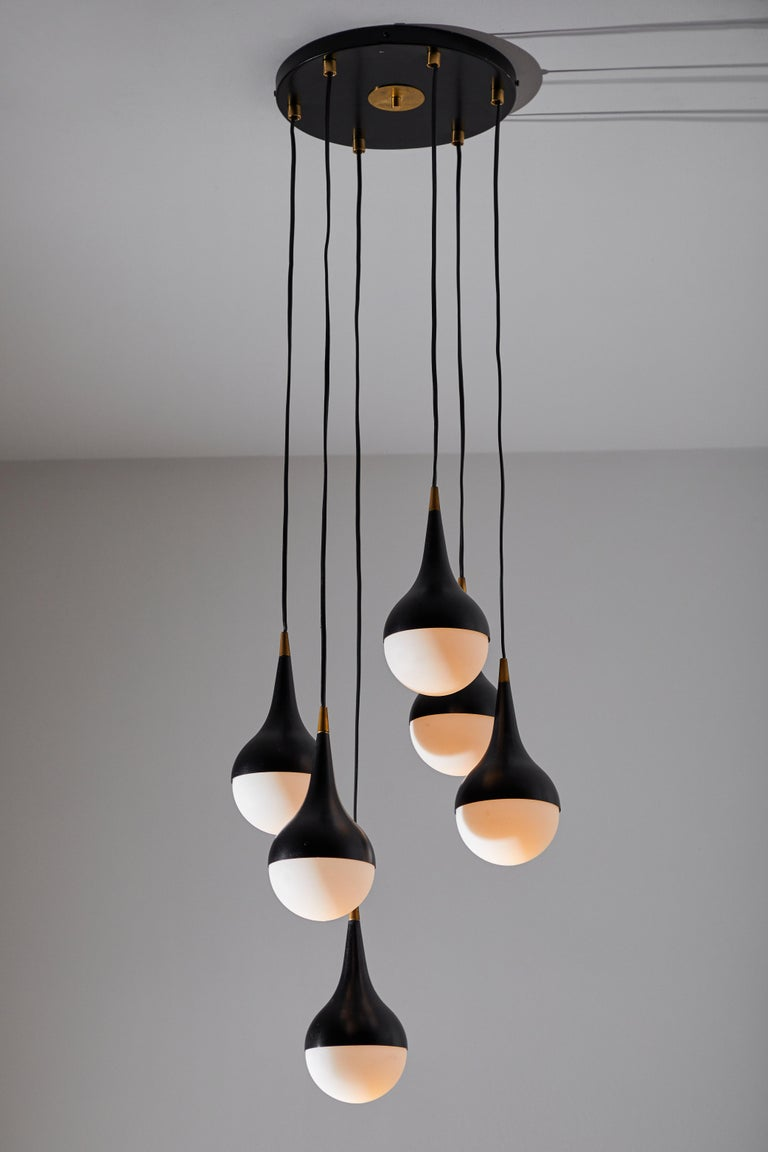 Suspension light by Stilnovo. Manufactured in Italy, circa 1960s. Enameled aluminum, brass hardware, brushed satin glass diffusers. Retains original manufacturer's label. Takes six E27 25 W maximum candelabra bulbs. Bulbs provided as a one time