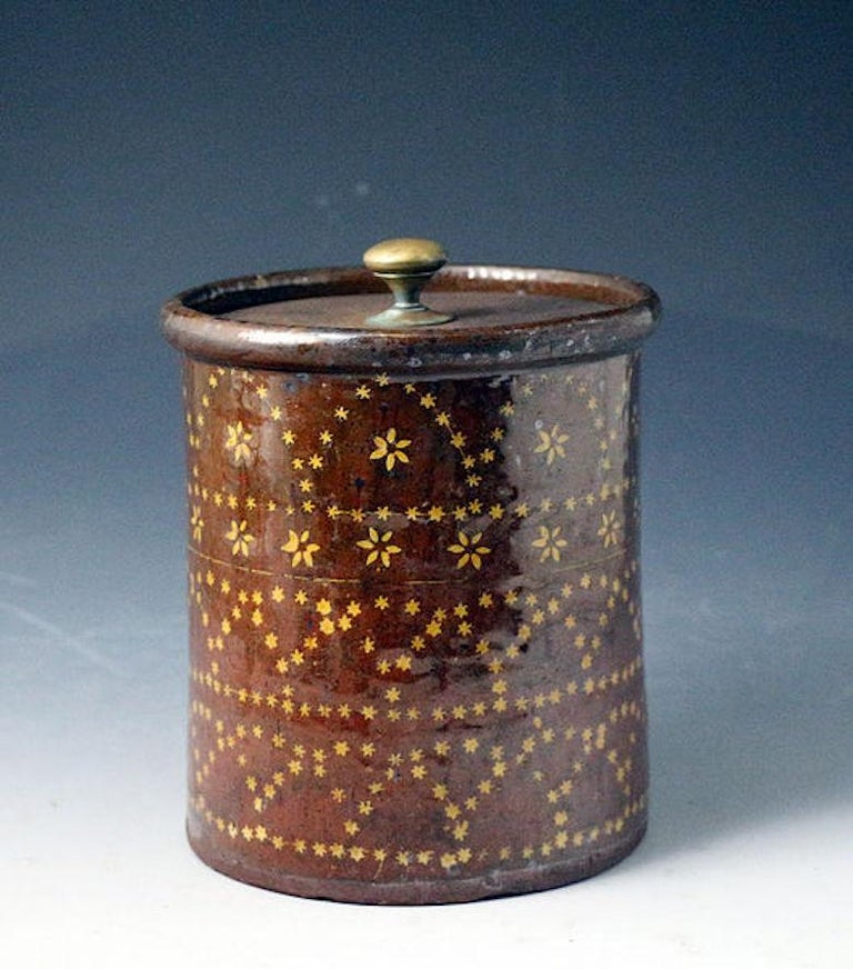 Earthenware slipware jar decorated with flower heads within a band and a profusion of stars in geometric patterns the piece with the initials S S and the date August 31st 1810 also in slip decoration. The metal lid is a tinker