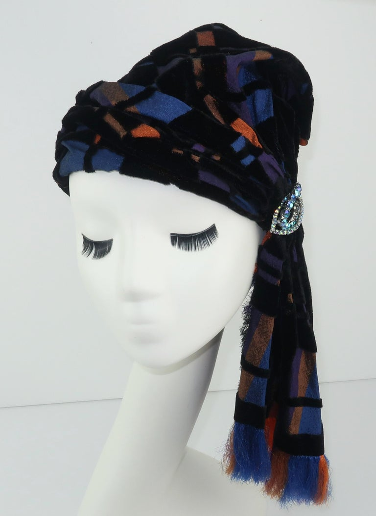 This turban shaped hat by Suzy Lee of California combines a bohemian style with a great plaid cut velvet in shades of black, copper orange, brilliant blue and plum.  The side drape has unfinished fringed edges by design and is accented by a