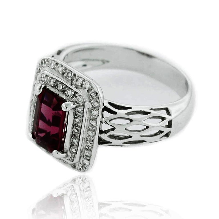 Stand out in this one-of-a-kind Suzy Levian, ruby and diamond in gold ring. Centering an emerald-cut 1.65 carat ruby center stone, this ring has a pave, doubled-layered square halo of 44 diamonds (H-I, SI1) (.55 cts). The ring is beautifully crafted
