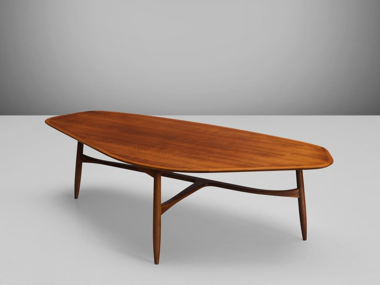 Svante Skogh, coffee table, walnut, Sweden, 1950s  This freely shaped coffee table with three thin tapered legs is part is beautifully shaped and shows high attention to detail, especially by means of the connecting tripod slat between the legs.
