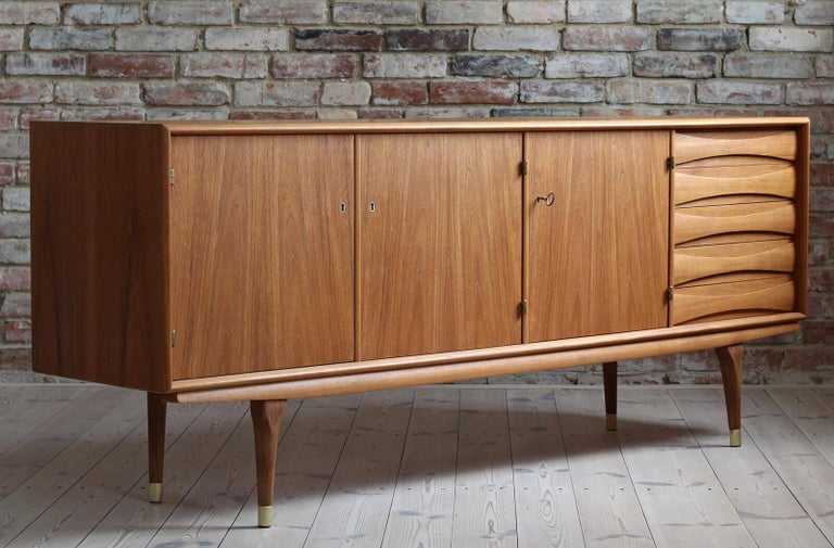This is a quite rare Sven Andersen teak sideboard designed and manufactured in Norway circa second half of the 1950s. The piece features three doors that reveal lots of storage space and five drawers in the section on the right. The sideboard