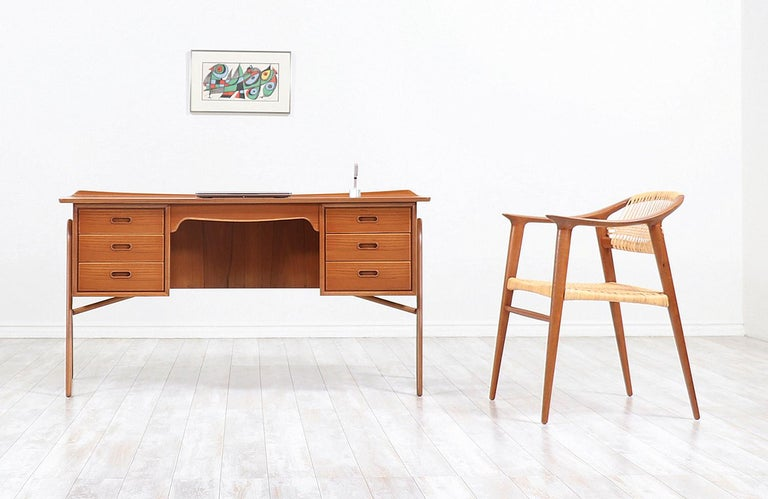Striking executive desk designed by architect Svend A. Madsen for H.P. Hansen Møbelindustri in Denmark circa 1960s. This iconic design is meticulously crafted in teak wood and is suspended in boomerang legs epitomizing Madsen's minimal and classic