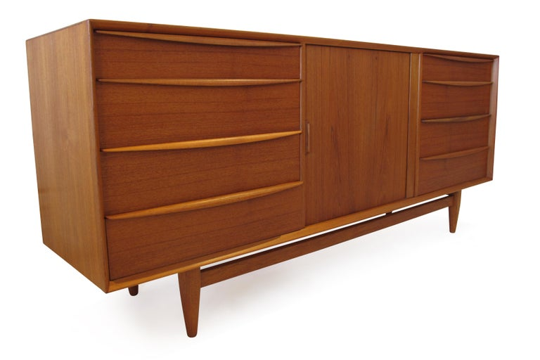 Midcentury teak dresser designed by Svend Age Madsen for Falster Mobelfabrik, Denmark. Crafted of old-growth teak with mitered corners, and raised on round tapered legs. The dresser has a total of 13 drawers. The left and right sides features four