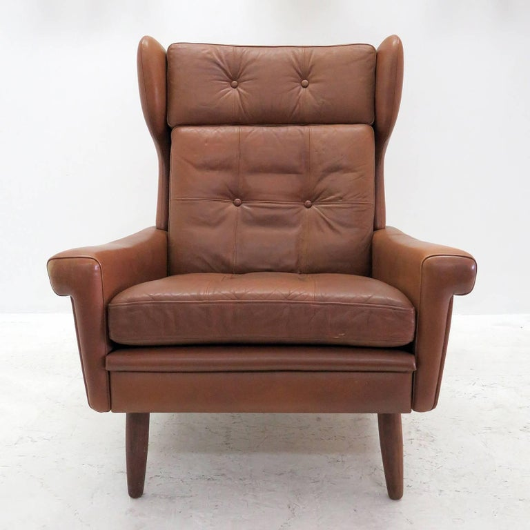 Wonderful high back winged leather lounge chair by Svend Skipper, with loose cushions upholstered in buttoned cognac colored leather with stained beech legs.