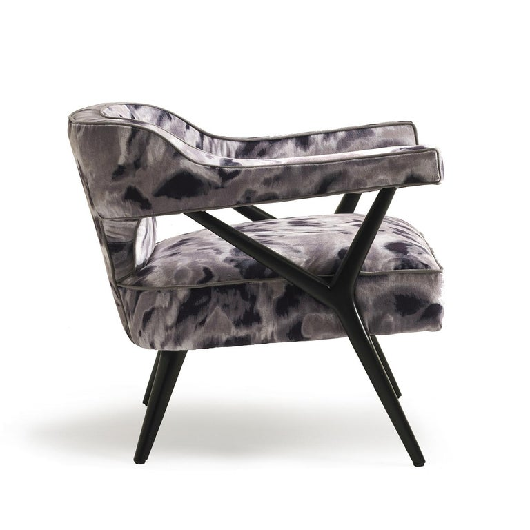 This lounge chair exudes elegant charm and timeless sophistication, thanks to the combination of a geometric structure in wood with a matte black finish supporting cut-out cushions upholstered in a stunning printed fabric in black, white, and grey.