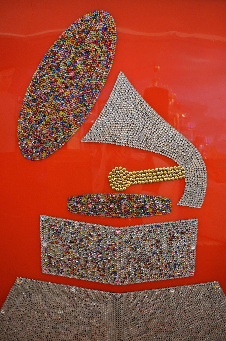 Each crystal is hand placed to create the image of the Grammy. Multicolored crystals.