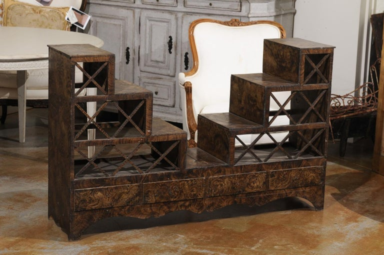 A Swedish stepped flower stand from the mid-19th century, with drawers and cross motifs. Created in Sweden during the third quarter of the 19th century, this flower stand attracts our attention with its burl style finish and stepped structure.