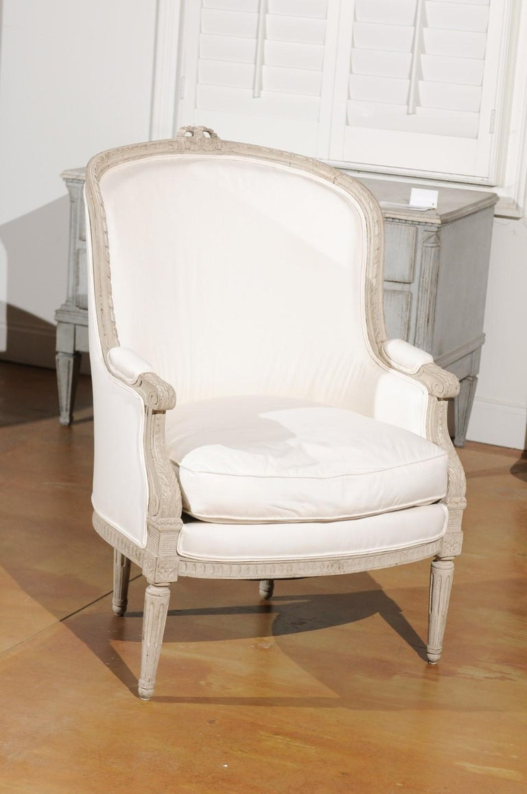 A Swedish neoclassical style painted wood barrel back bergère chair from the early 20th century, with carved bow, fluted legs and new upholstery. Born in Sweden during the early years of the 20th century, this exquisite barrel back chair presents