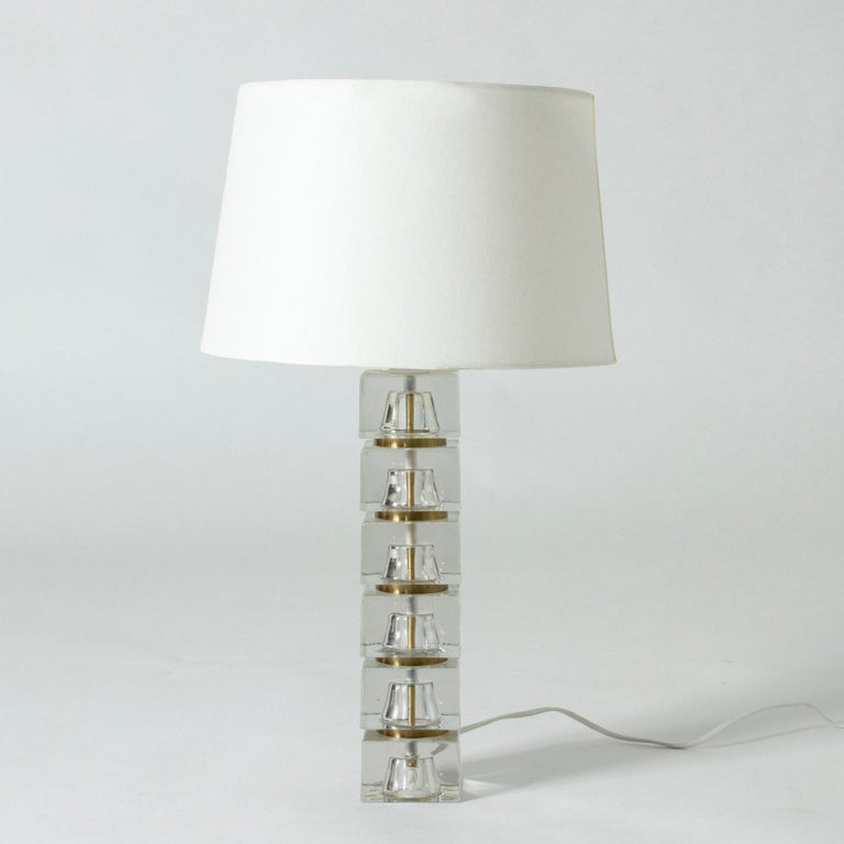 Cool Swedish 1960s crystal table lamp where the base is made from translucent blocks. A slender brass pipe concealing the wiring runs through the middle of the base, creating a cool visual effect. The sections between the blocks are painted gold.
