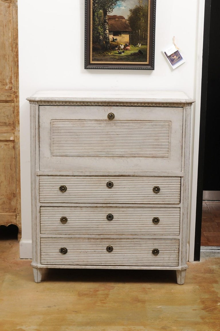 A Swedish Gustavian style painted wood drop-front secretary from the 19th century, with dentil molding, reeded accents and multiple drawers. Born in Sweden during the 19th century, this exquisite painted Gustavian style secretary features a