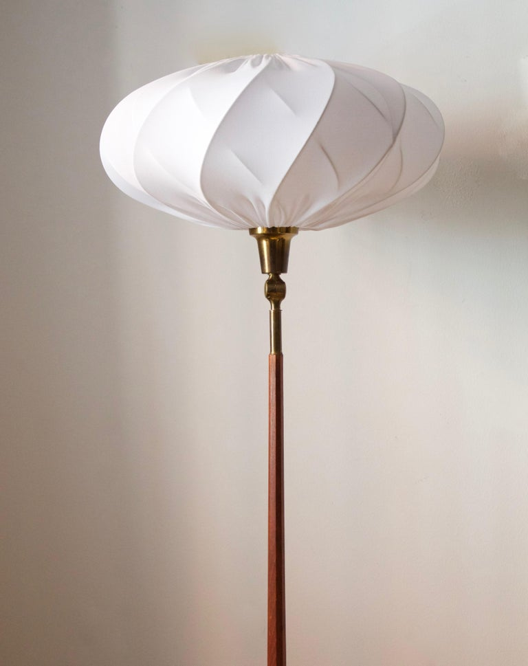A floor lamp. Designed and produced in Sweden, 1950s. Brand new lampshade of traditional model, hand-made in Sweden.