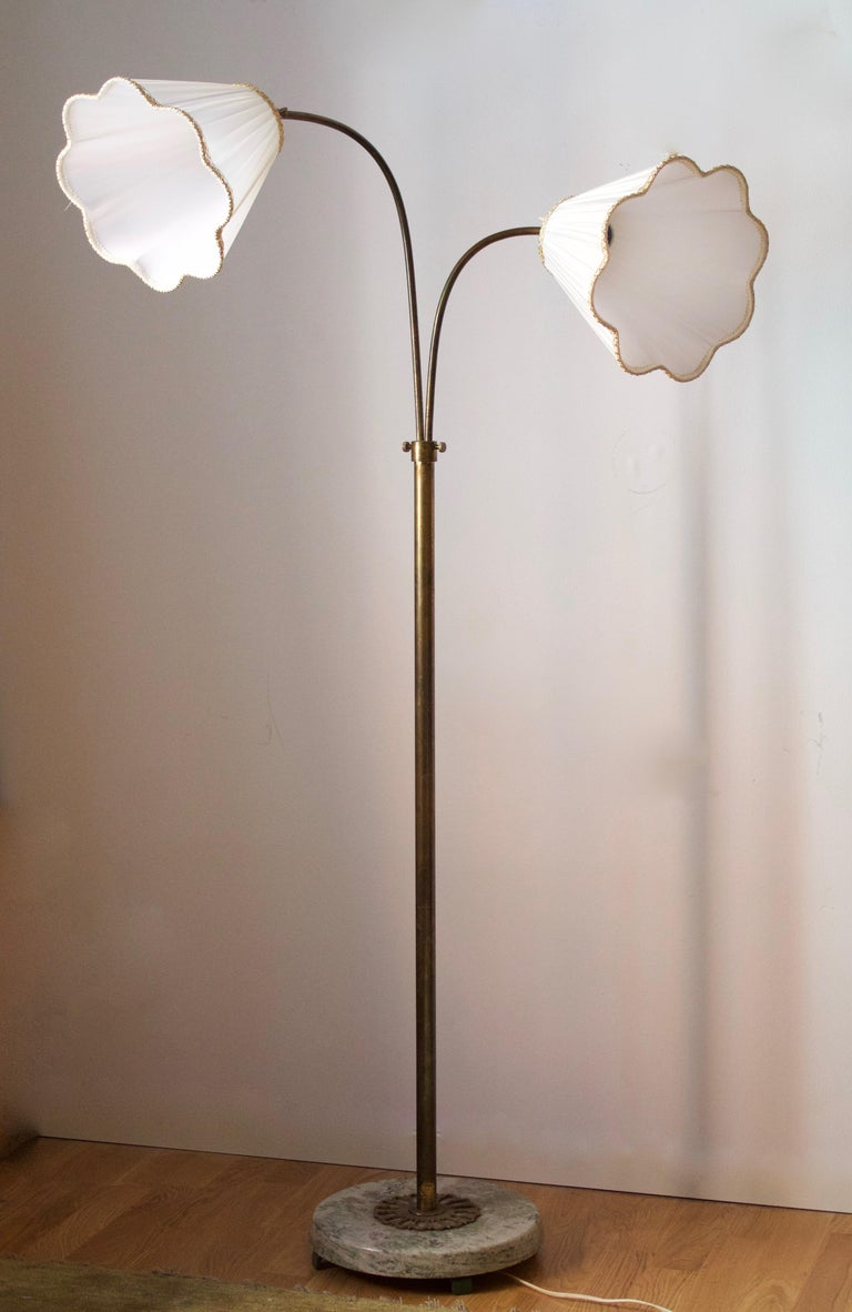 An adjustable floor lamp. Designed and produced in Sweden, 1940s. Brass with heavy marble base. Brand new lampshades of period model, handmade in Sweden.