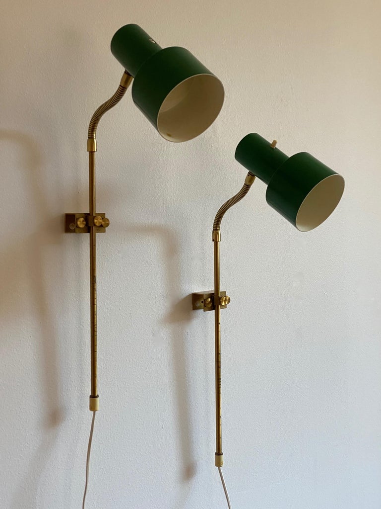 A pair of adjustable wall lights. Designed and produced in Sweden, 1950s.   Features green lacquered metal and brass.