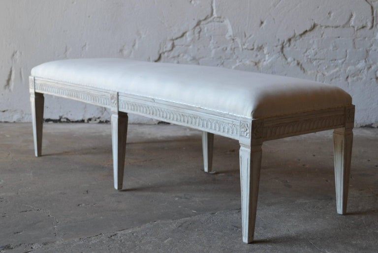 Antique Swedish Gustavian painted bench, with carved lamb's tongue apron, square tapered legs with carved flower rosettes at top of each leg. The bench is painted in a white-greyish color and distressed finish. Renewed upholstery and textile.