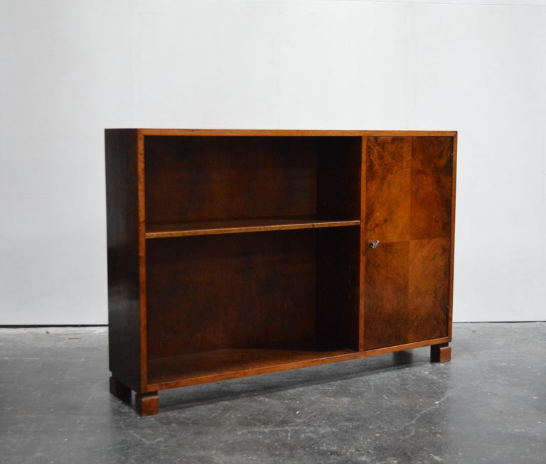Midcentury or Art Moderne bookcase was cabinet crafted of native flame birch. This gorgeous wood has mellowed to a rich dark amber color. Adjustable shelf on the left and locking cabinet section on the right. Key included. Perfect as a slim console