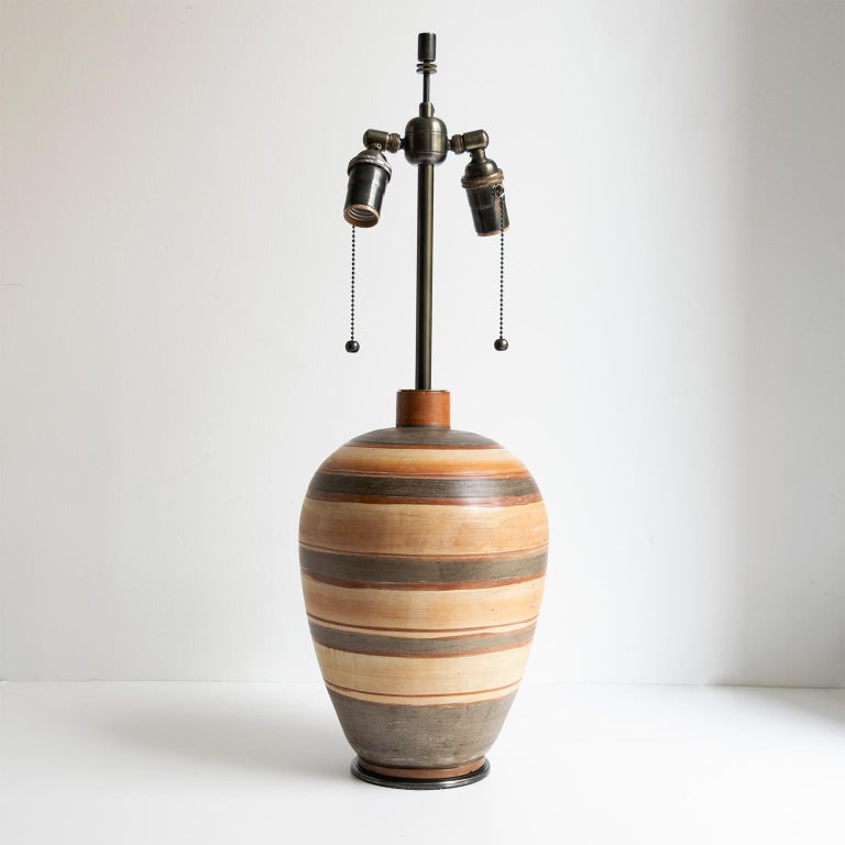 A Swedish Art Deco hand thrown 1937 ceramic vase by Gudrun Slettengren with bands of color glazes. Newly converted to a lamp with custom hand patinated hardware. Newly wire with a standard base socket double cluster. Shade not included.  Measures: