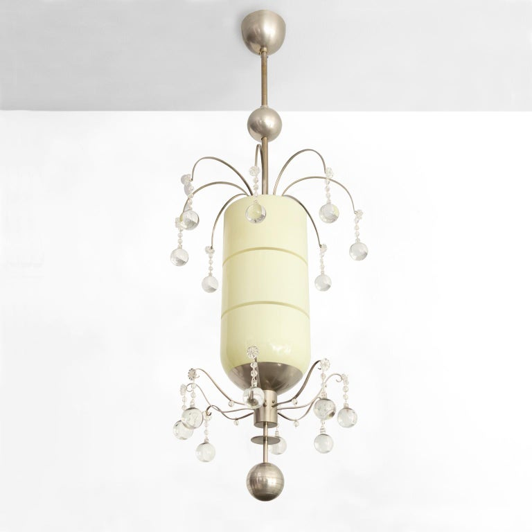 Swedish Art Deco pendant by Bohlmarks with 2 tiers of mixed size crystals surrounding a capsule shaped modernist cased glass shade with horizontal etched grooves. The brass metal structure is plated with nickel from canopy to finial. Newly restored,