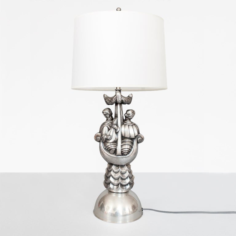 Per Torndahl Swedish Art Deco silver plated metal table lamp designed for Atelier Torndahl, in Perstorp circa 1920s. The lamp depicts a male and female figures in a boat, with stylized waves, mast and sails. Newly electrified with a nickel plated