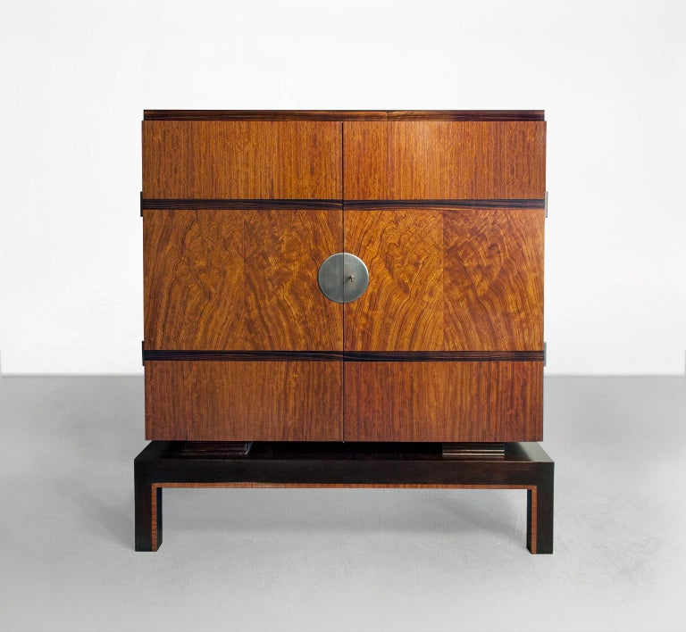 Swedish Art Deco two-door cabinet which hovers on a plinth and is veneered with mahogany and horizontal bands of Macassar ebony. A decorative steel circular plate covers the lock mechanism and exterior tubular steel hinges detail the cabinets sides.