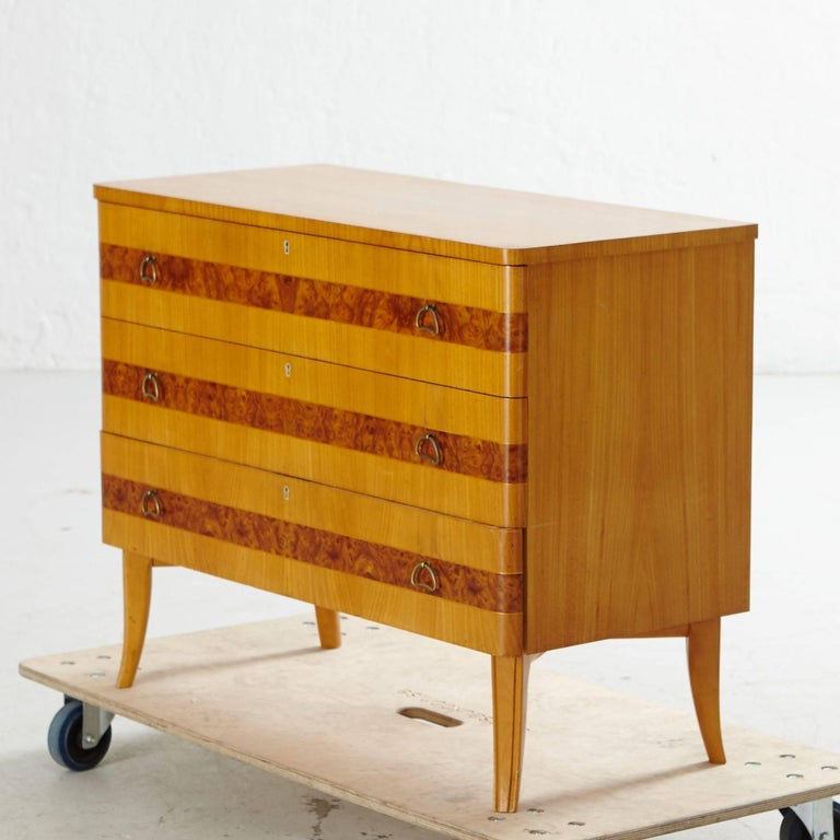 Swedish art moderne three-drawer dresser in elm and Carpathian elm. Original metal pulls. Four saber legs. Original key. Restored and in pristine condition. Made at Bodafors in Southern Sweden in the 1940s.