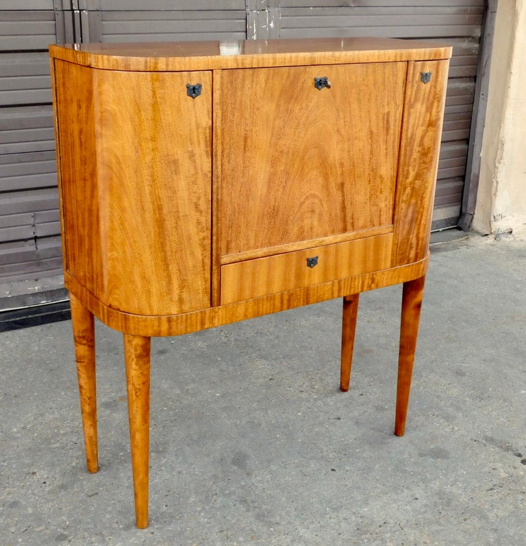 Swedish Art Moderne drop front secretary desk with side cabinets for bottle storage. Rendered in open grain, natural color Honduran mahogany. With interior drawers and desk flap which is stabile and great for supporting (and storing) a lap top