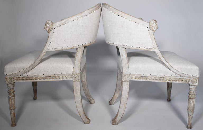 Elegant pair of 19th century Gustavian barrel back armchairs with detailed lions' head carvings on arms, saber legs, scraped to original patina with European Burlap. Carving on the chair back at top of seat rest, sides, apron and legs add to the