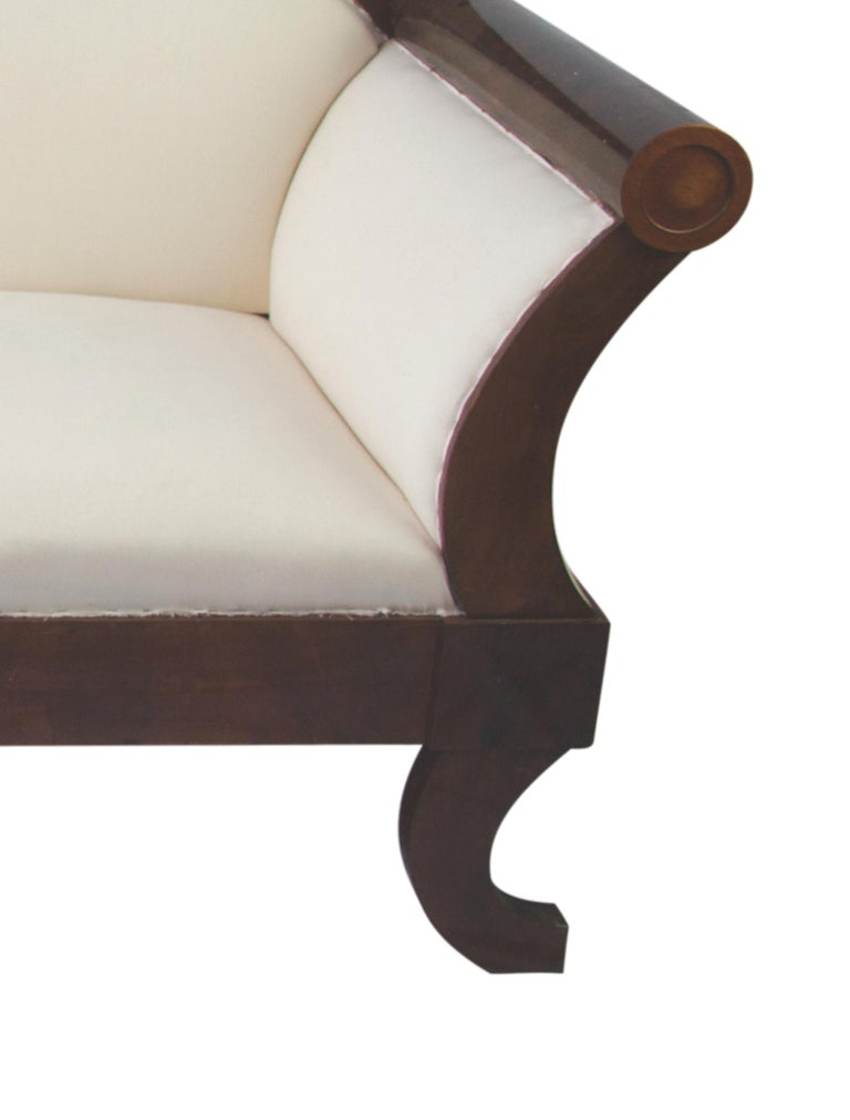 Lovely antique Swedish Biedermeier carved three-four-seat sofa in Classic darker French polish finish that brings out the figure in the top grade mahogany quilted veneers.  It features roundel motifs on the arm and gently curving feet with a deep