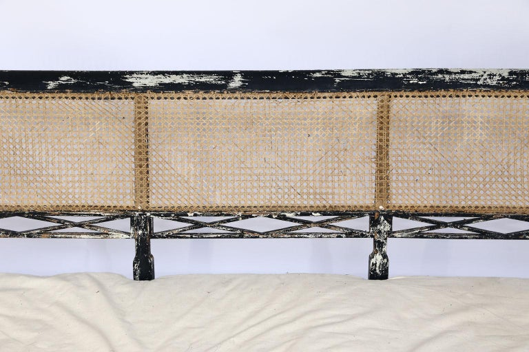 This beautiful antique Swedish cane back settee wears it's original painted patina. Standing on eight legs, the wood frame is strong and sturdy. The settee allows seating for three and has a three inch cushion which adds character and charm to the