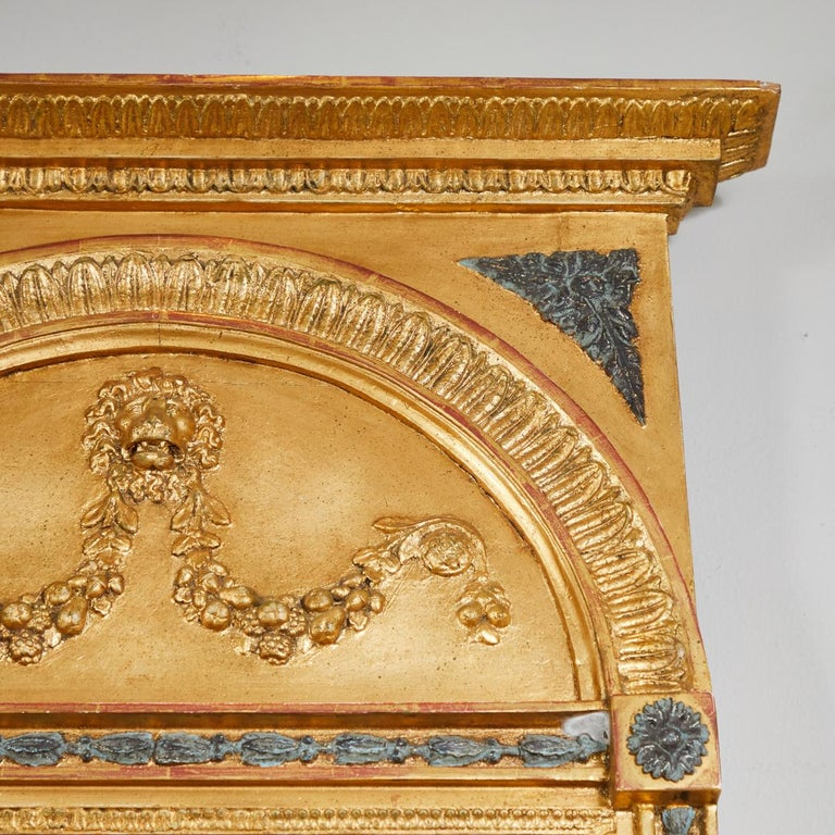 A rectangular gilt mirror with cornice top over a carved arch with a carved lion's head guarding fruit swags. The lower mirror with carved neoclassical motifs and anthemion in bottom reserve, circa 1800.
