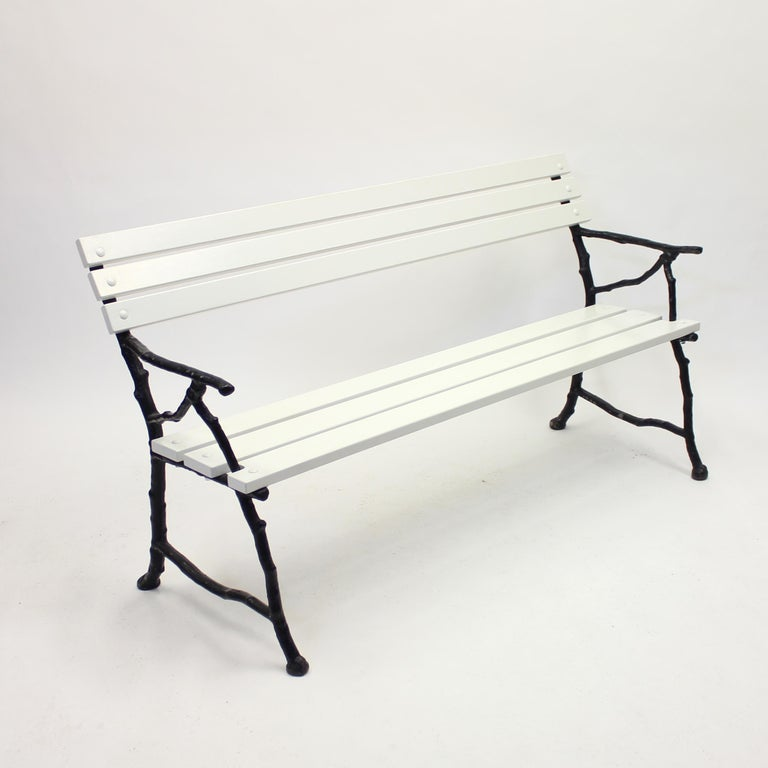 Swedish cast iron garden sofa with white painted wooden plank seat and back. The black cast iron frame, depicting tree branches, is from the early 20th century. The seat and back are totally restored with new wood and new screws to keep this piece